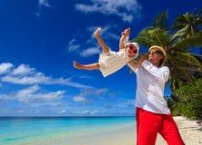 的父亲和获得小的女儿在海滩的乐趣 免版税库存照片