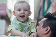 他的父亲的容忍的男婴走穿过城市的 库存照片