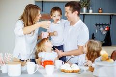 的父母和一起享用他们的三个的孩子吃在厨房里和 免版税库存照片