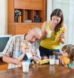 的父母和吃两个的孩子午餐 库存图片