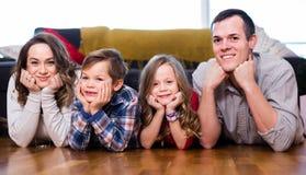 的父母和愉快两个的孩子在家花费时间 免版税图库摄影