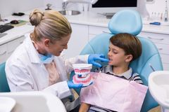 的牙医拿着牙齿模子的大角度观点,当审查男孩时 库存照片