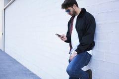 轻的牛仔裤、一件白色T恤杉和一件黑暗的夹克的时兴的人 免版税库存图片