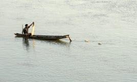 他的独木舟的渔夫撤退捕鱼网的 免版税库存图片