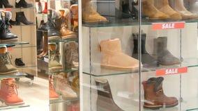 的玻璃陈列室鞋店题字销售 在柜台的时髦的秋天冬天鞋子昂贵 股票视频