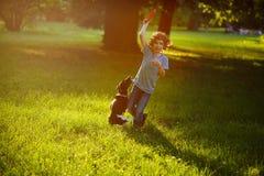 8-9年的男孩使用与他的在草坪的黑白狗在公园 图库摄影