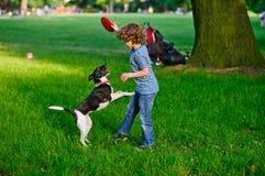 8-9年的男孩充当有狗的公园 库存照片