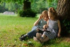 8-9年的男孩和女孩坐一棵草在有小膝上型计算机的公园 免版税库存图片