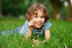 8-9年的男孩在密集的绿草在 免版税库存图片