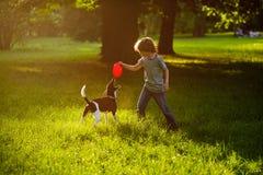 8-9年的男孩在有狗的公园训练 免版税库存图片