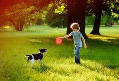8-9年的男孩在有狗的公园训练 免版税图库摄影