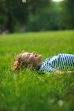 8-9年的男孩在绿色草坪说谎在公园 免版税图库摄影