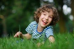 8-9年的男孩在绿草在并且笑 免版税库存图片