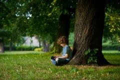8-9年的男孩坐在一棵大树下,倾斜在片剂 免版税库存照片