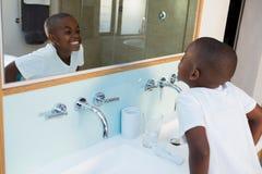 的男孩握紧牙的大角度观点,当看镜子时 库存照片