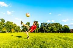 的男孩演奏橄榄球夏天公园的天观点 库存照片