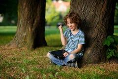 8-9年的男孩,倾斜反对树和举行片剂坐膝部 免版税库存照片