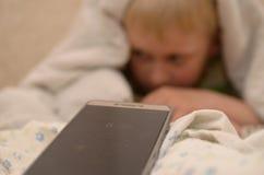 8的男孩 从毯子下面的上午30点不要醒到学校 库存图片