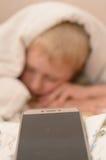 8的男孩 从毯子下面的上午30点不要醒到学校 免版税库存图片