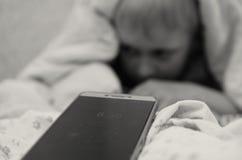 8的男孩 从毯子下面的上午30点不要醒到学校 库存照片