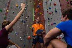 的男性教练员互动与运动员的低角度观点坐在健身房 库存图片
