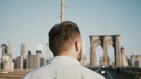 的男性游人走沿布鲁克林大桥的后面观点在纽约4K 旅行癖、旅游业和自由概念 股票视频