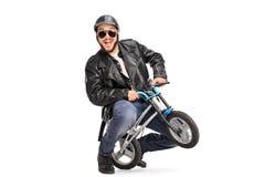 傻的男性骑自行车的人坐一辆小自行车 库存图片