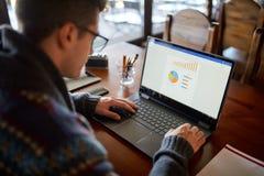 的白种人商人研究有图的膝上型计算机的后面观点在屏幕上 玻璃工作的自由职业者在项目 免版税库存照片