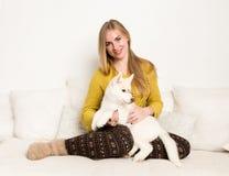 的白肤金发的妇女睡衣和羊毛袜子与多壳的小狗在一张白色床上说谎 免版税库存照片