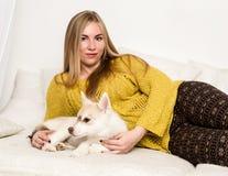 的白肤金发的妇女睡衣和羊毛袜子与多壳的小狗在一张白色床上说谎 免版税库存图片