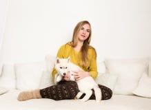 的白肤金发的妇女睡衣和羊毛袜子与多壳的小狗在一张白色床上说谎 库存照片