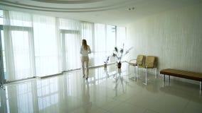 的白肤金发的妇女走在办公室大厅的高跟鞋的后面观点与杯子 股票视频