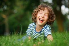 8-9年的稀薄的男孩在绿草在并且大笑 免版税库存照片