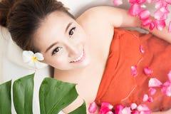 浴的美丽的亚裔秀丽妇女与玫瑰花瓣 身体关心和温泉 库存照片