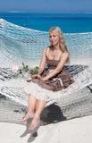 的美丽的妇女在一个吊床的长的sundress在海背景 免版税库存图片