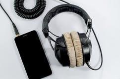 质朴的耳机音乐智能手机白色背景 库存图片