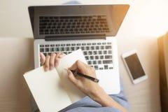的职业妇女拿着写笔记本的笔 她工作使用膝上型计算机 免版税库存图片