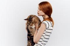 轻的背景的年轻美丽的妇女拿着一只猫,过敏 图库摄影