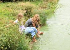 洗他们的脚的两个女孩 图库摄影