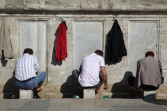 洗他们的脚的伊斯兰教的人 库存图片
