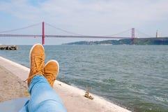 的脚鞋子 在休息的水附近 在背景的里斯本红色桥梁视图 免版税库存照片