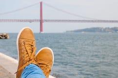的脚鞋子 在休息的水附近 在背景的里斯本红色桥梁视图 免版税库存图片