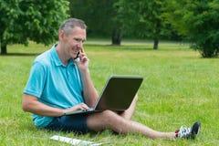 他的膝上型计算机人公园工作 库存照片