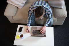 的自由职业者的人研究膝上型计算机的上部观点,做笔记 免版税库存图片