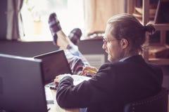 的自由职业者运作在木书桌的观点 免版税图库摄影