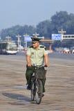 他的自行车的在清早,北京,中国超重军人 免版税库存照片
