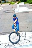 他的自行车的男孩在冰鞋公园 免版税库存图片