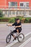 他的自行车的年轻人,北京,中国 库存图片