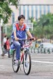 他的自行车的年轻工人在市中心,珠海,中国 免版税库存图片