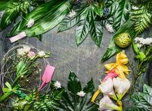 轻的花和绿色品种离开与装饰安排创造在土气背景,顶视图的问候花束 库存图片